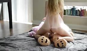 Une jolie blonde chevauchant un ours en peluche