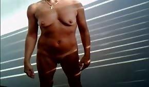 Une amatrice nue se masturbe sur un stand